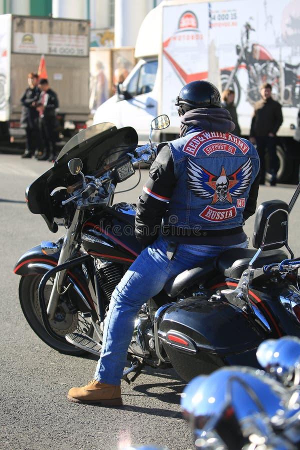 Motociclista in una maglia con il logo del supporto rosso e bianco 81sitting del club del motociclo dell'esercito sulla sua bici fotografia stock