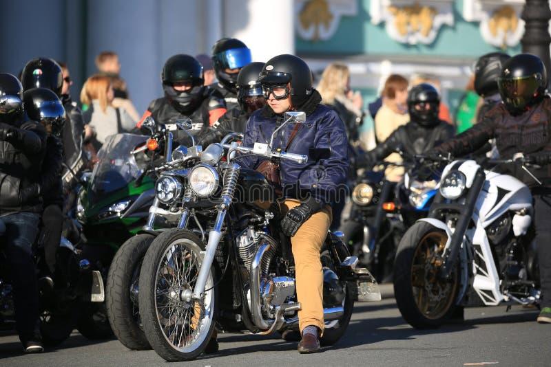 Motociclista in vestiti stilizzati del 60-70s dello XX secolo sul suo motociclo tra altri motociclisti fotografia stock libera da diritti