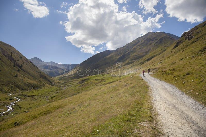 Motociclistas da montanha que vão abaixo de uma estrada íngreme foto de stock