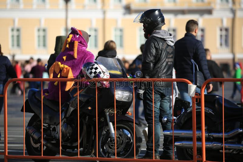 Motociclistas e um suporte da motocicleta perto da cerca alaranjada imagens de stock royalty free