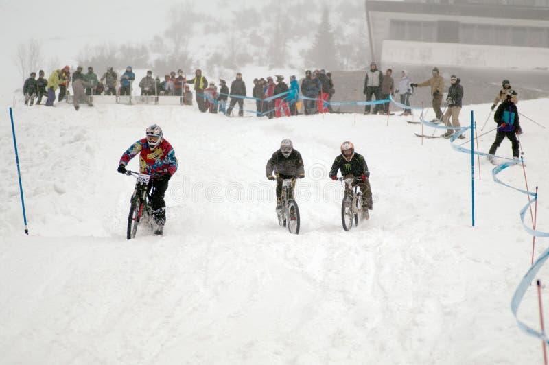 Motociclisti alla corsa in discesa del mountain bike estremo di inverno fotografie stock