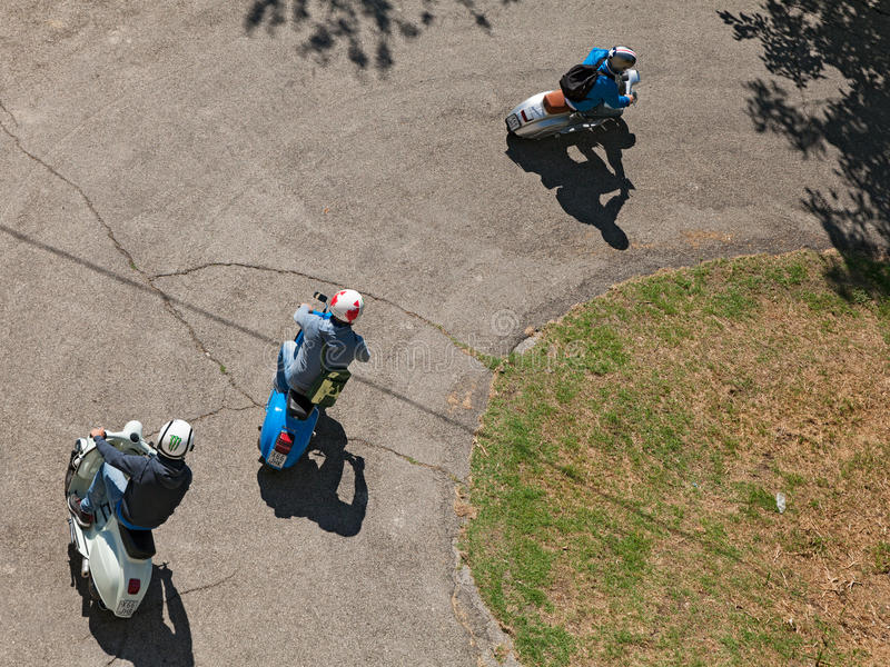 Motociclisti che guidano la vespa d'annata dei motorini fotografie stock