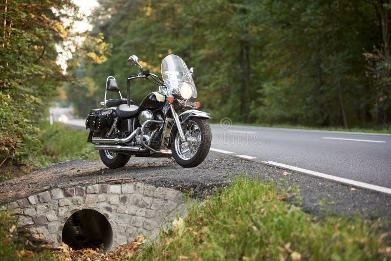 Motociclo ad alta velocit? brillante nero parcheggiato sul bordo della strada stretto vuoto del paese il giorno di estate soleggi fotografia stock libera da diritti