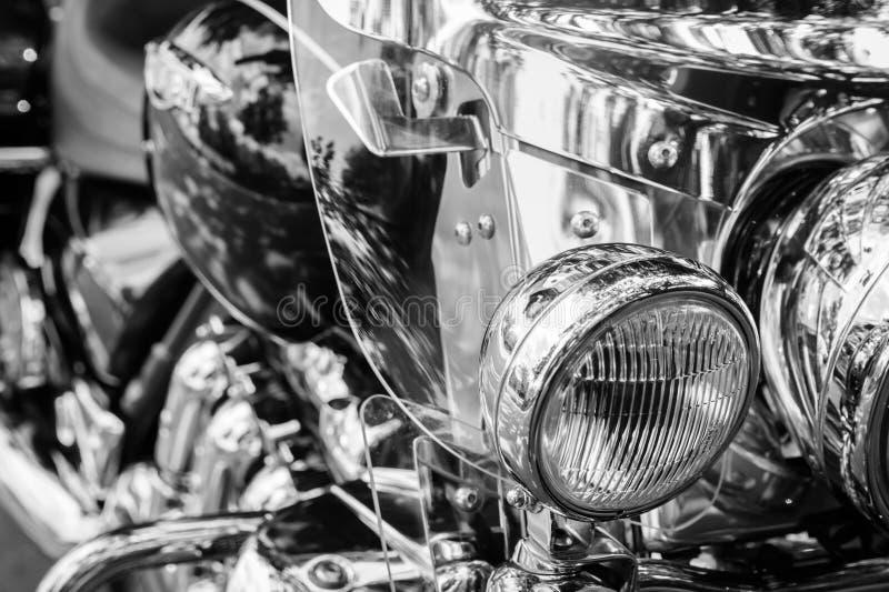 Motociclo brillante del faro su un fondo in bianco e nero confuso immagini stock