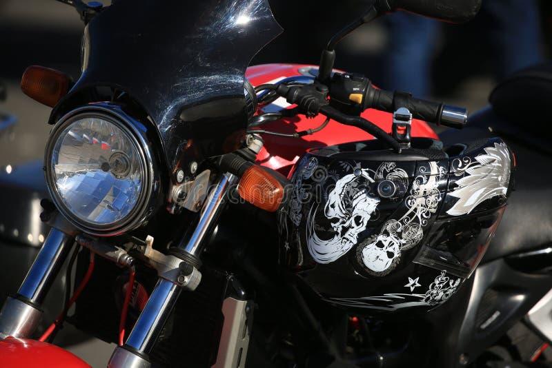 Motociclo con il casco sul suo primo piano del manubrio immagini stock