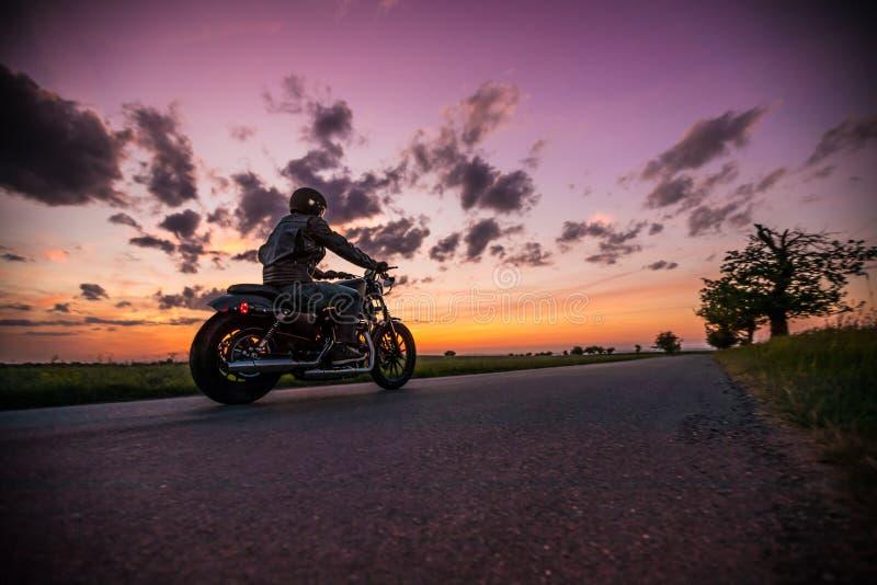 Motociclo dello sportster di guida dell'uomo durante il tramonto immagine stock
