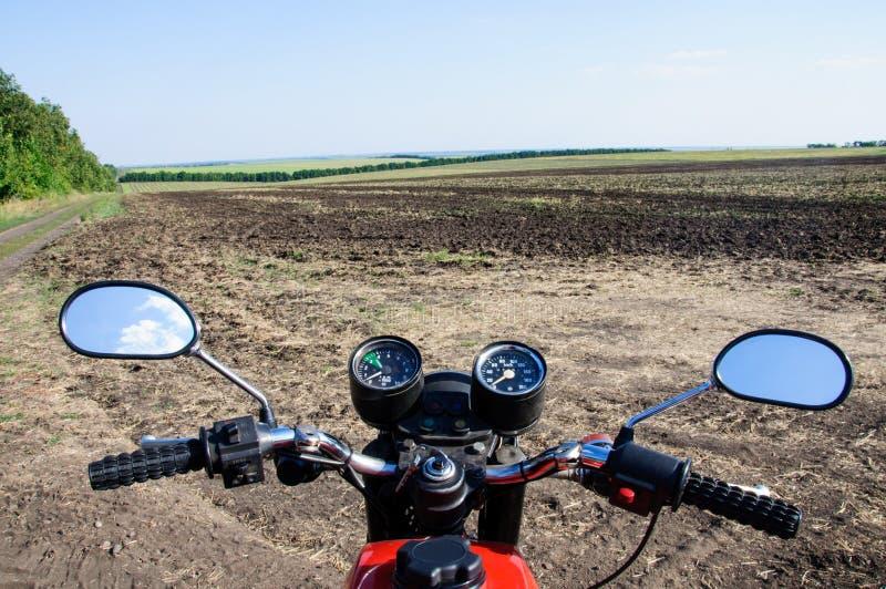 Motociclo di cuoio viaggio La strada attraverso il campo fotografia stock