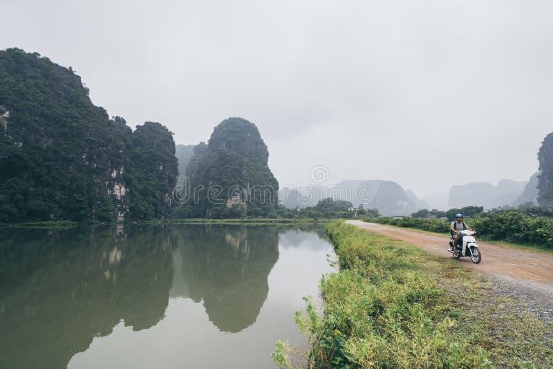Motociclo di guida dell'uomo fra le montagne del calcare nella provincia di Ninh Binh, Vietnam immagine stock libera da diritti