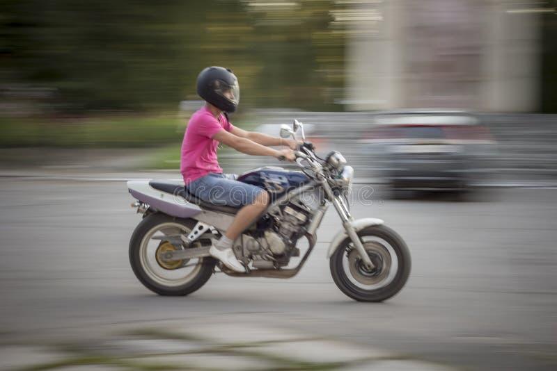 Motociclo di guida dell'uomo Il giovane tipo negli shorts del denim e di una maglietta rosa, con un casco del motociclo sulla sua immagini stock