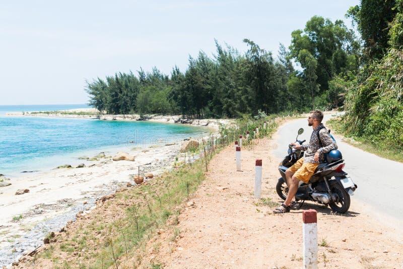 Motociclo di guida dell'uomo lungo il mare sulla strada al passaggio di Hai Van, Vietnam immagini stock libere da diritti