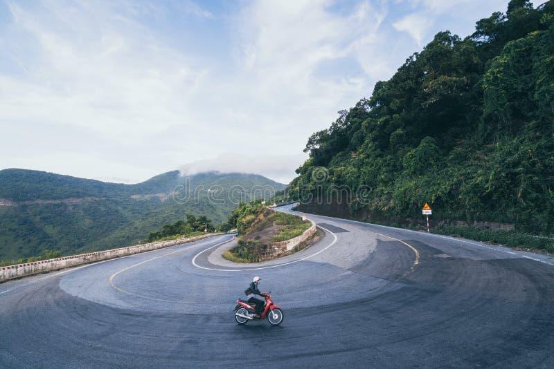 Motociclo di guida dell'uomo sulle strade di bobina del passaggio di Hai Van dalla città di tonalità a Hoi An, Vietnam immagini stock