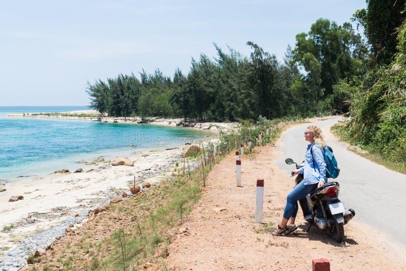 Motociclo di guida della donna lungo il mare sulla strada al passaggio di Hai Van, Vietnam fotografia stock