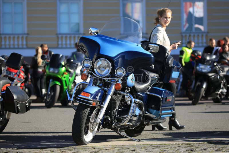 Motociclo e giovane donna parcheggiati di Harley-Davidson da dietro immagine stock libera da diritti