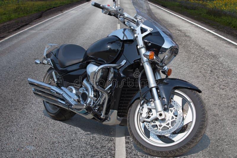 Motociclo nero sulla strada principale in paese immagine stock libera da diritti