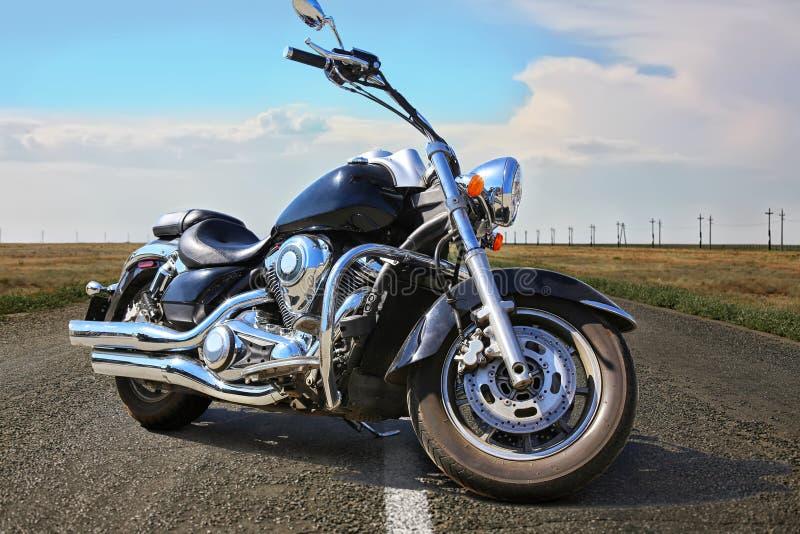 Motociclo nero sulla strada principale in paese immagini stock libere da diritti