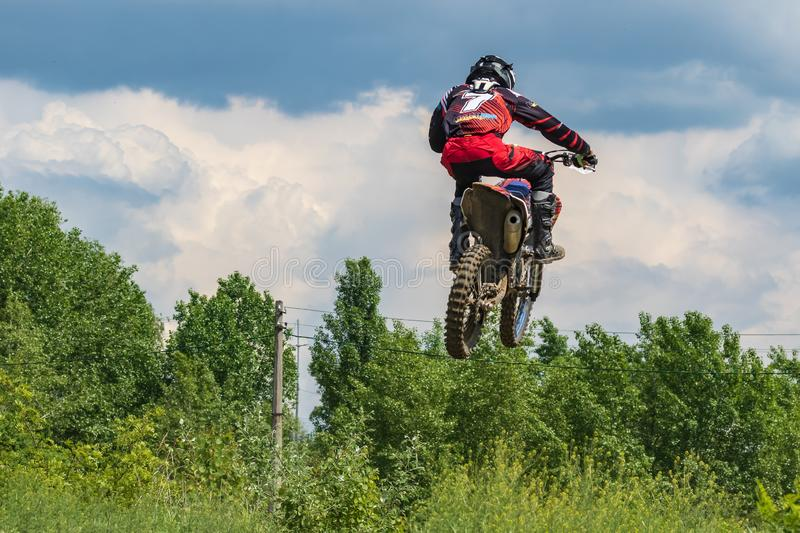 Motocross. The athlete on a motorcycle jumps high against the blue sky and white clouds. royalty free stock images