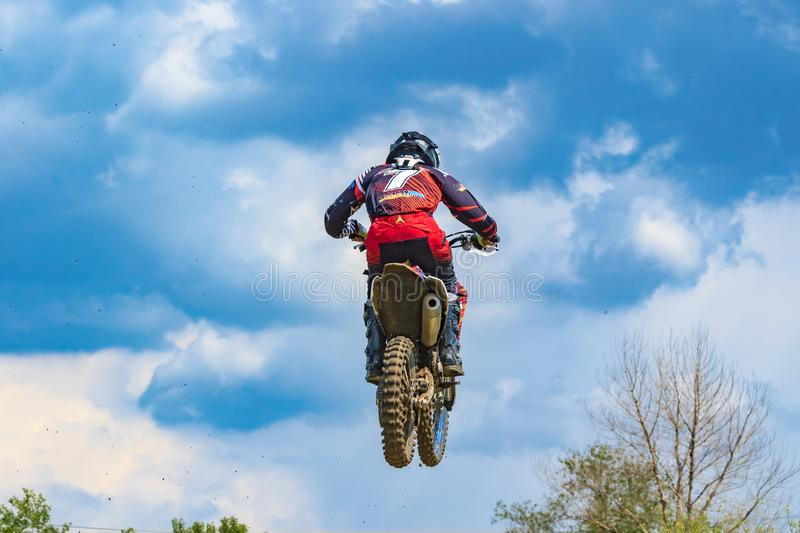 Motocross. The athlete on a motorcycle jumps high against the blue sky and white clouds. stock photos