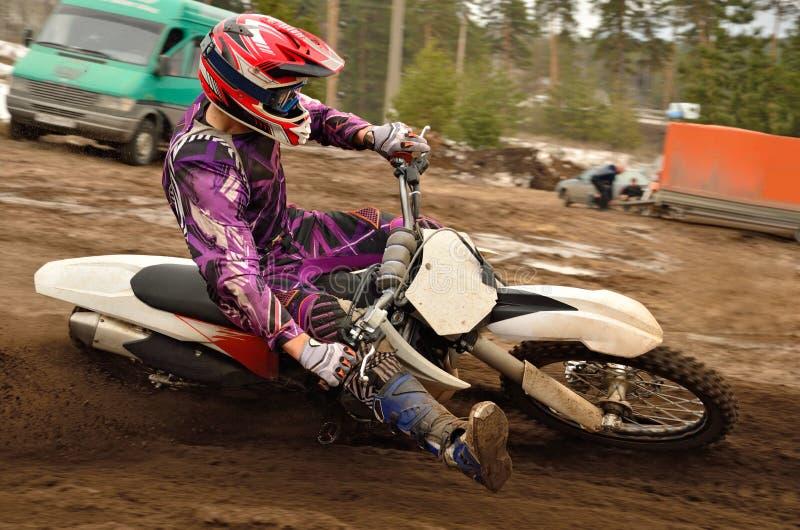 Motocross athlete raised leg forward executes turning royalty free stock photos