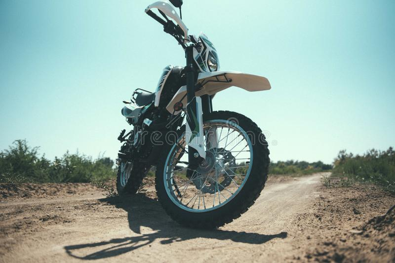 Motocross bike stands on a sandy road. Close up, handle, stylish, dirt, off-road, race, biker, dune, driving, offroad, desert, sport, sunset, racer, standing royalty free stock photos