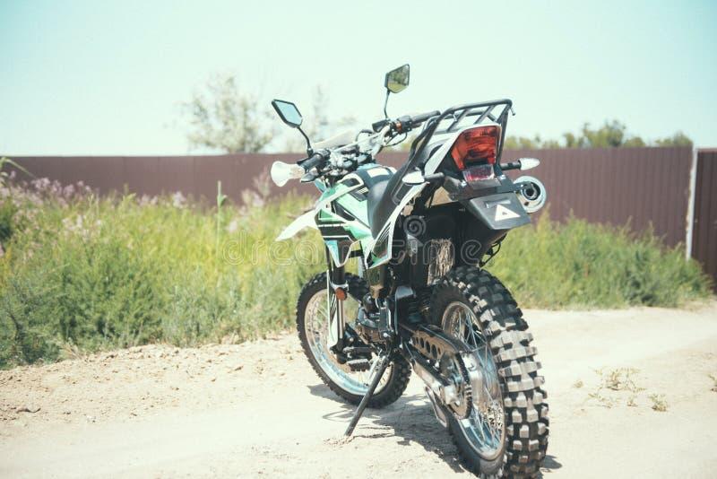 Motocross bike stands on a sandy road. Close up, handle, stylish, dirt, off-road, race, biker, dune, driving, offroad, desert, sport, sunset, racer, standing stock image