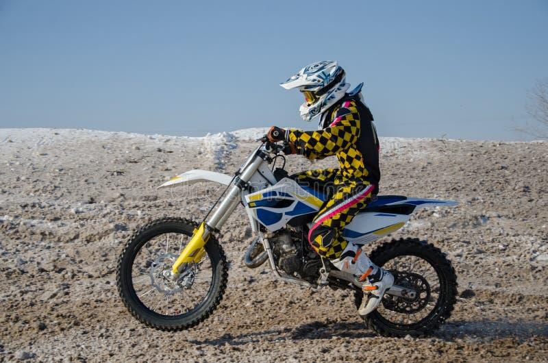 Motocross, de vliegen van de motorfietsbestuurder over heuvel uit sneeuw stock foto's