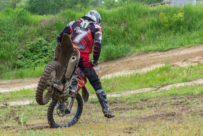 motocross Der Athlet zieht auf das Vorderrad eines Motorrades um Nahaufnahme lizenzfreies stockbild