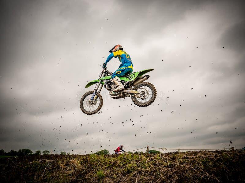 Motocross driver flying through dirt stock image