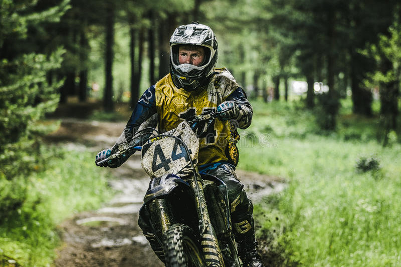 Motocross driver on muddy offroad track. Kyshtym, Russia - June 21, 2015: Motocross driver on muddy offroad track during the race Urals Cup of Enduro Stone belt royalty free stock photos