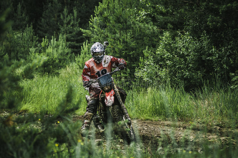 Motocross driver on muddy offroad track. Kyshtym, Russia - June 21, 2015: Motocross driver on muddy offroad track during the race Urals Cup of Enduro Stone belt royalty free stock images