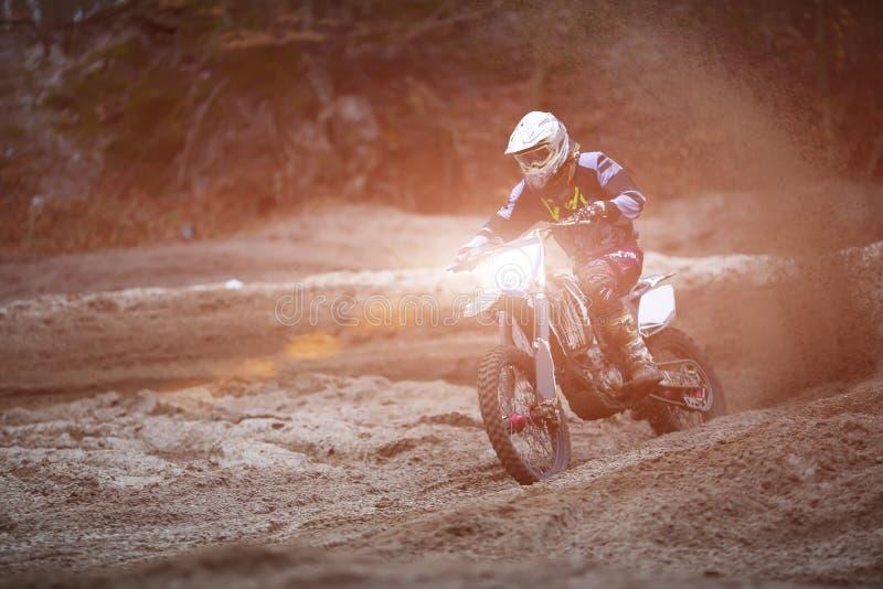Motocross, enduroruiter op vuilspoor Extreem off-road ras Harde enduromotor Het bos achter hem stock foto's