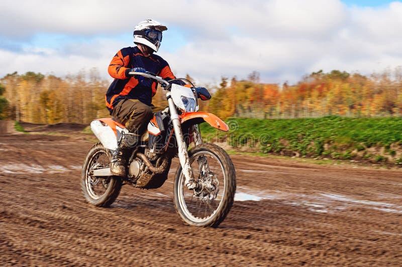 Motocross enduroryttare på smutsspår Skogen bak honom arkivfoto