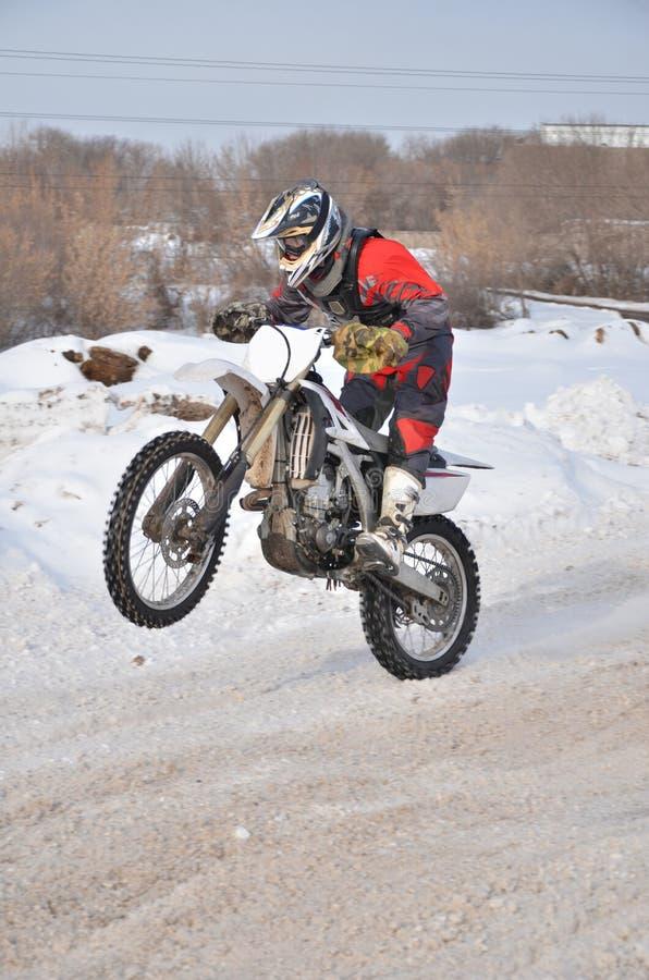 Motocross jeździec na motocyklu jeżdżeniu na zimie drogowy trzyma u obrazy royalty free