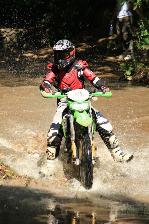 Motocross men, Enduro ride through water splashing in canals, royalty free stock photos