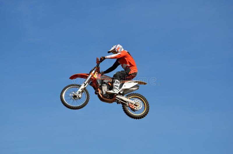 Motocross, motocyklu kierowca lata nad wzgórzem z śniegu zdjęcia stock