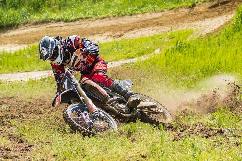 Motocross. Motorcyclist in a bend rushes along a dirt road, dirt flies from under the wheels. Close-up. royalty free stock images