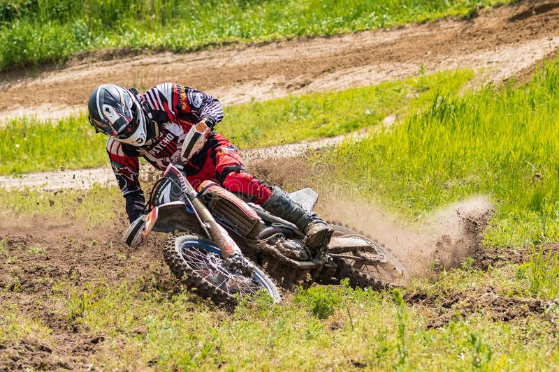 Motocross. Motorcyclist in a bend rushes along a dirt road, dirt flies from under the wheels. Close-up. royalty free stock photo