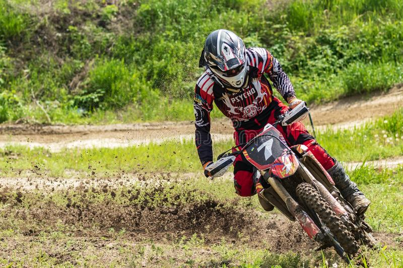 Motocross. Motorcyclist rushes along a dirt road, dirt flies from under the wheels. Against the backdrop of bright spring greens. royalty free stock image