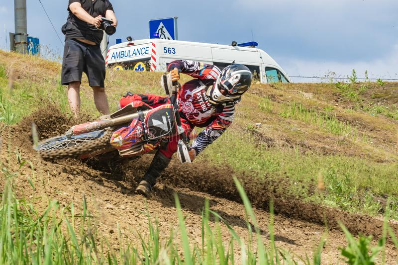 Motocross. Motorcyclist rushes along a dirt road, dirt flies from under the wheels. Photographers near. Doctors are watching. stock photo