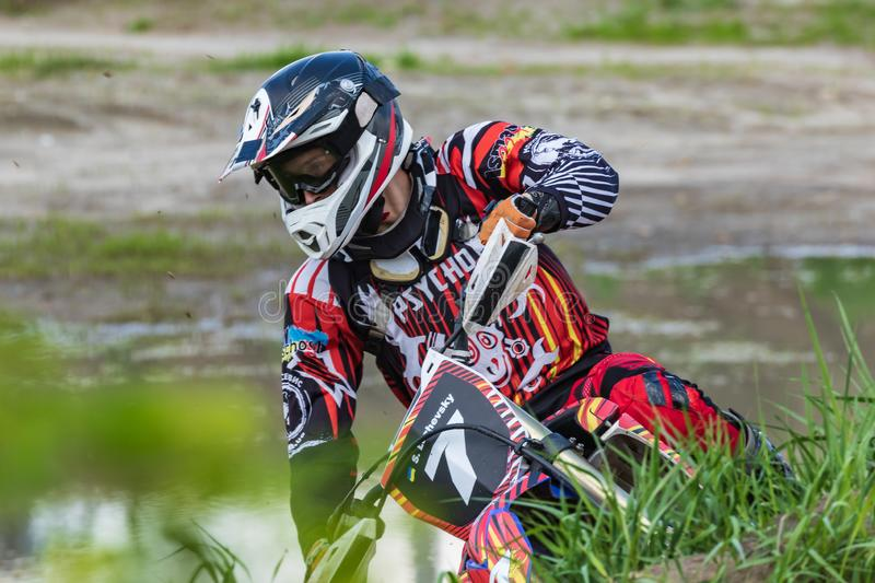 Motocross. Motorcyclist rushes along a dirt road.  Greenery in the foreground. royalty free stock photography