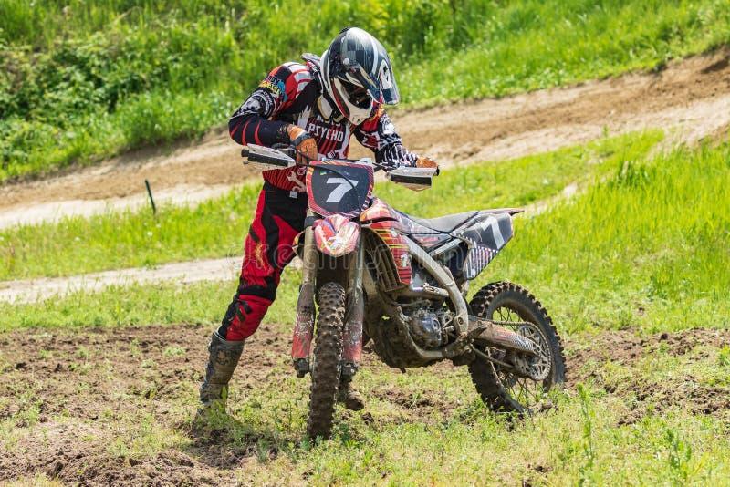 motocross Motorradfahrer bereitet vor sich, das Rennen nach einem geringfügigen Fall fortzusetzen Nahaufnahme stockfotografie