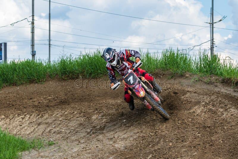 motocross Motorradfahrer in einer Biegung hetzt entlang einem Schotterweg, Schmutz fliegt von unterhalb der Räder Aktiver extreme lizenzfreie stockbilder