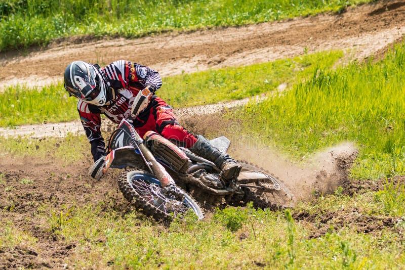 motocross Motorradfahrer in einer Biegung hetzt entlang einem Schotterweg, Schmutz fliegt von unterhalb der Räder Nahaufnahme lizenzfreies stockfoto