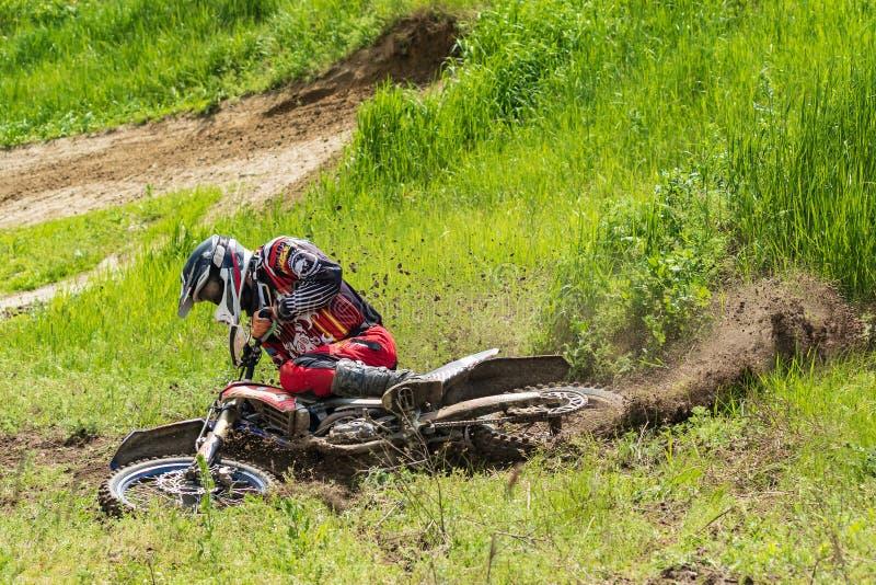motocross Motorradfahrer in einer Biegung hetzt entlang einem Schotterweg, Schmutz fliegt von unterhalb der Räder lizenzfreie stockfotos