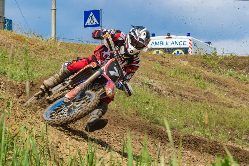 motocross Motorradfahrer in einer Biegung hetzt entlang einem Schotterweg, Schmutz fliegt von unterhalb der Räder lizenzfreie stockbilder