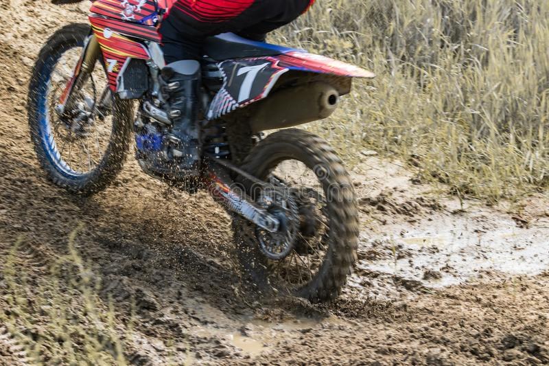 motocross Motorradfahrer hetzt entlang einem Schotterweg, Schmutz fliegt von unterhalb der R?der lizenzfreie stockfotografie