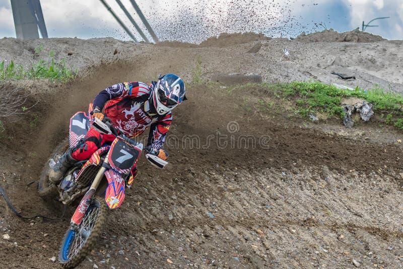 motocross Motorradfahrer hetzt entlang einem Schotterweg, Schmutz fliegt von unterhalb der R?der Aktiver extremer Rest lizenzfreies stockfoto