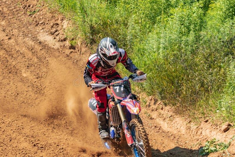motocross Motorradfahrer hetzt entlang einem Schotterweg, Staub fliegt von unterhalb der Räder lizenzfreie stockbilder