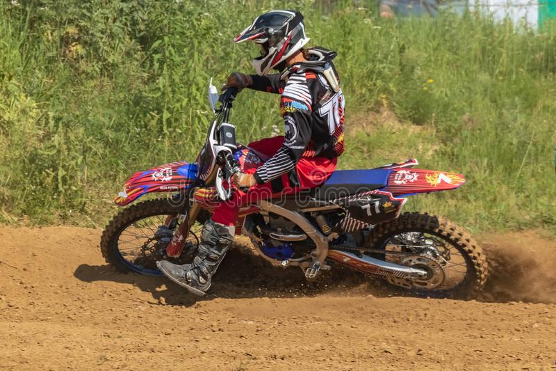 motocross Motorradfahrer hetzt entlang einem Schotterweg, Staub fliegt von unterhalb der Räder lizenzfreies stockbild
