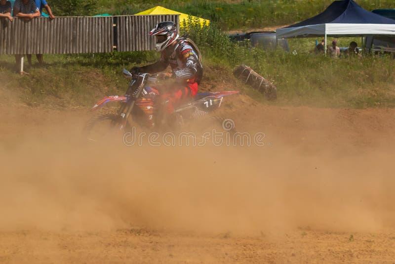 motocross Motorradfahrer hetzt entlang einem Schotterweg, Staub fliegt von unterhalb der Räder stockfoto