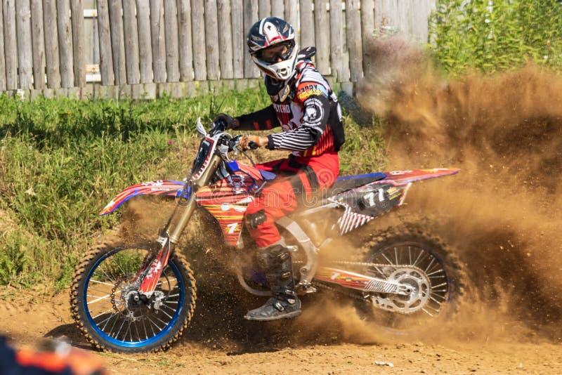 motocross Motorradfahrer hetzt entlang einem Schotterweg, Staub fliegt von unterhalb der Räder stockbilder